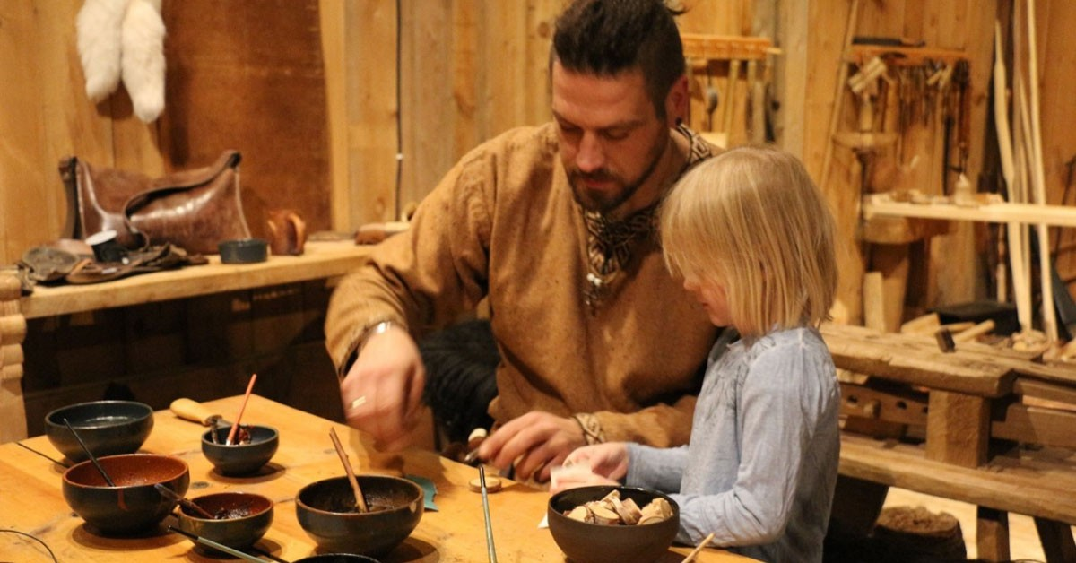 Viking and young girl making rune amulets together.